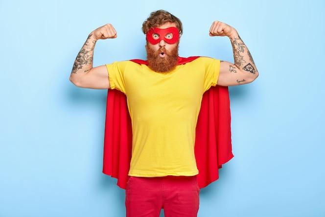 Эмоционально удивленный герой-мужчина обладает благородными качествами, демонстрирует силу с поднятыми руками.