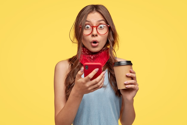 Эмоционально удивленная девушка-подросток открывает рот, чувствует изумление, держит смартфон и достает кофе, производит впечатление ошеломленного взгляда, получает неожиданное сообщение, изолированное над желтой стеной
