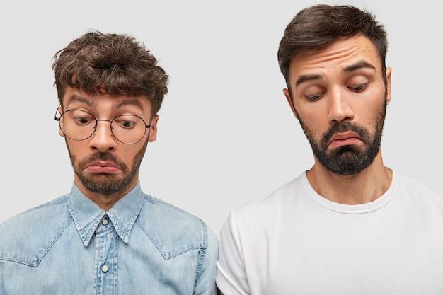 Эмоциональные двое коллег-мужчин, сосредоточенные на удивлении, с удивленным выражением лица, небрежно одетые, с густой темной бородой, заметили что-то удивительное