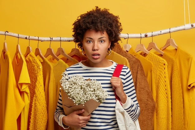 Emotive woman shopper stares with scared expression, reacts on high prices in shop, carries shopping bag on shoulders, stands against clothes rack