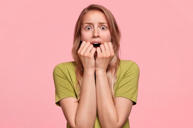 感情的な若い女性モデルは拳を噛み、カメラを神経質に見ています