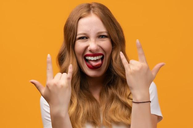 Эмоциональная молодая женщина с волнистой рыжей делает знак рок-н-ролл