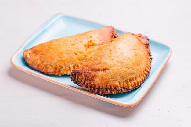 Эмпанада, мясной пирог на тарелке и белой поверхности