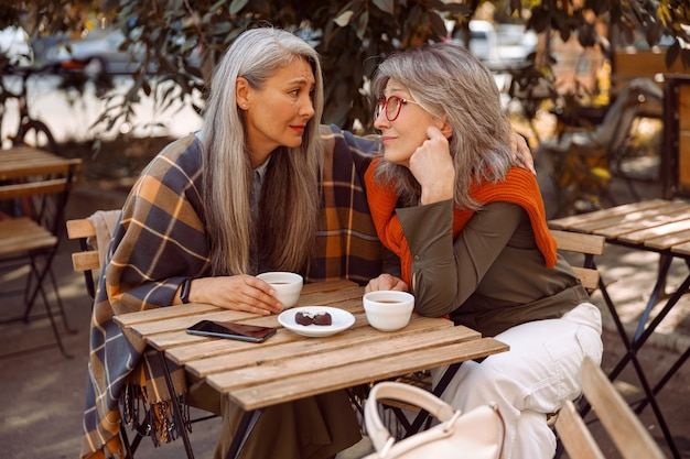 Empathic grey haired asian woman hugs friend to cheer up at table in street cafe