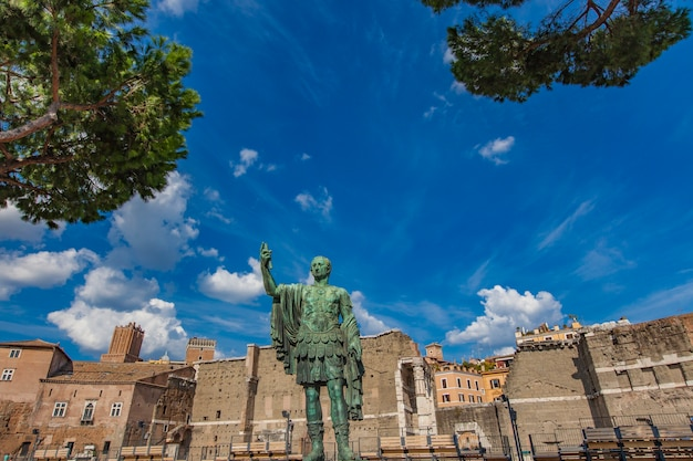 Emperor julius caesar statue in front of ancient trajan's market in rome