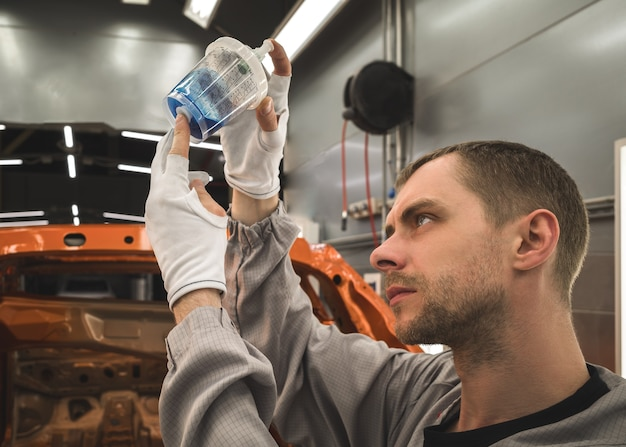 Employee of an automobile factory prepares the base enamel for painting cars