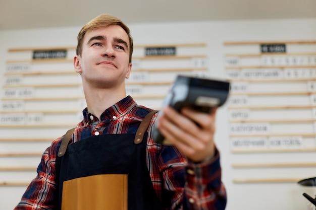 앞치마를 입은 직원 바리스타가 카페에 현대적인 은행 결제 단말기를 들고 있습니다.