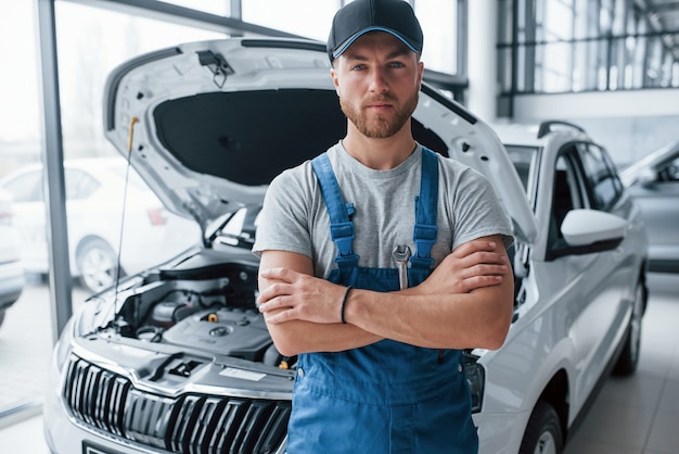 Employee in the blue colored uniform stands in the automobile salon.