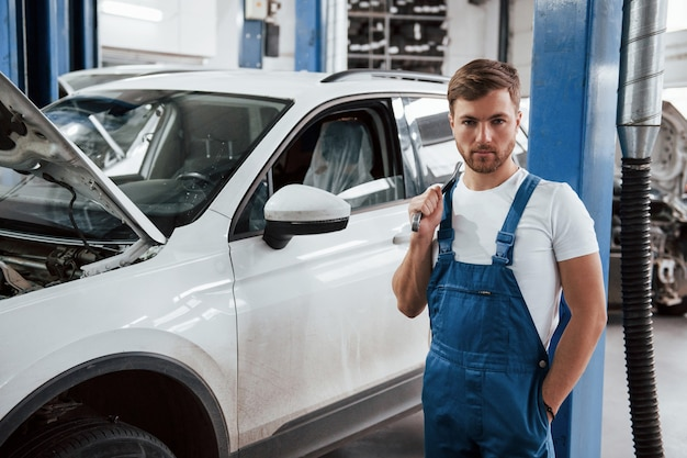 Employee in the blue colored uniform works in the automobile salon.