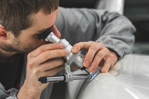 Сотрудник автомастерской проверяет качество под микроскопом.