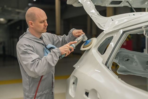 An employee of the car body painting shop polishes the painted surface