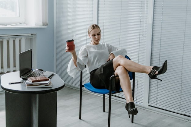 Employee care relaxed happy young business woman entrepreneur put legs on table talking on cell