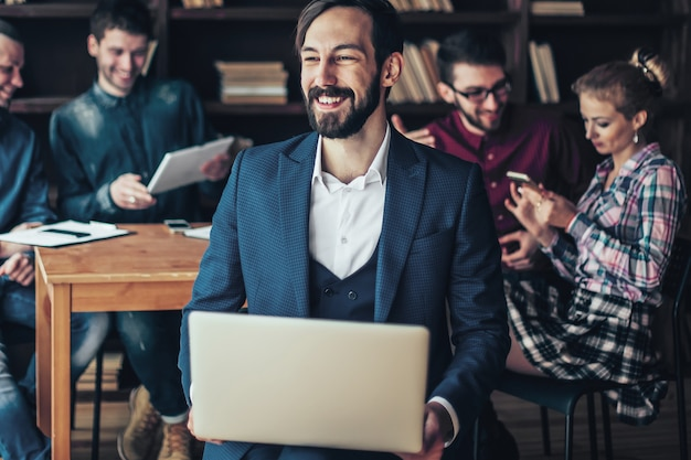 Employee of the company with laptop on the background of busines
