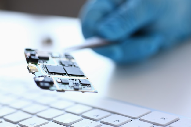 An employee of computer repair service assembly keeps spare part motherboard processor with tweezers for installation using method of soldering technology development