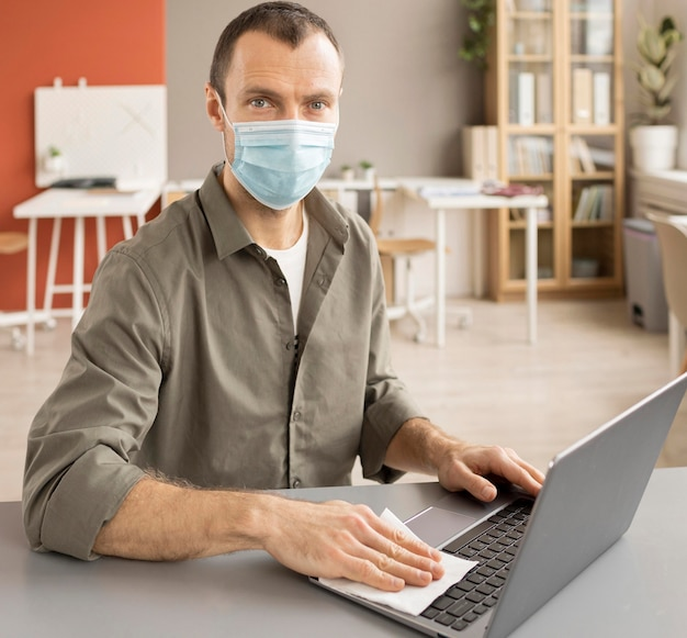 Employee disinfecting electronic device