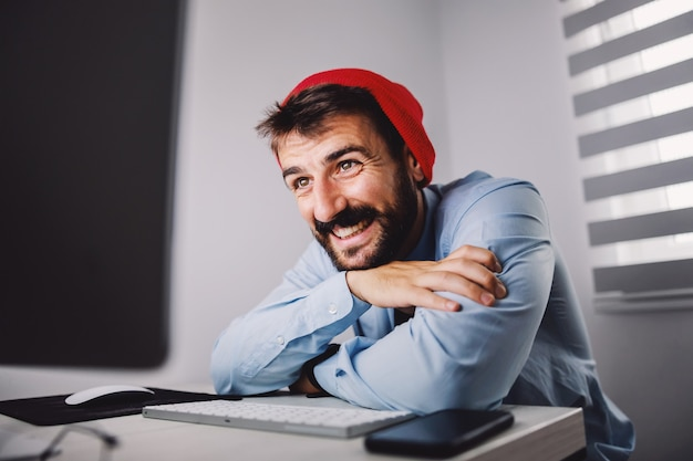 Сотрудник одет в деловой случай, сидя в своем офисе и глядя на ноутбук во время карантина.