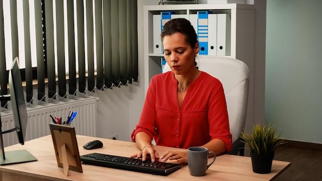 직원은 사무실 방에 있는 컴퓨터 앞에 앉아 커피를 마시고 뉴스를 읽고 있습니다. 직장에 오는 기업가, 데스크탑을 보고 있는 pc 키보드에 입력하는 전문 회사 작업 공간
