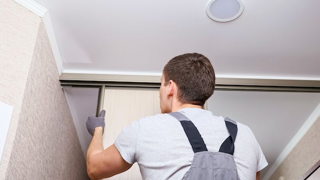 Employee furniture assembler in white t-shirt and jumpsuit checks wooden sliding door of modern wardrobe with mirror close back low angle shot