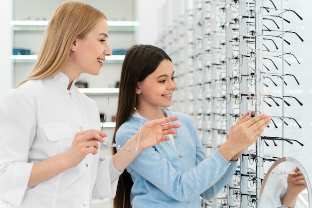 Employee helping girl to try on glasses