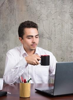 Сотрудник, держащий чашку чая и смотрящий ноутбук за офисным столом.