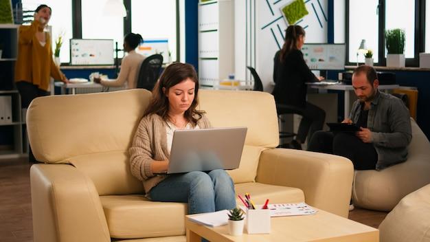 さまざまな同僚がバックグラウンドで作業している間、pcの笑顔で入力する快適なソファでリラックスゾーンに座っているラップトップを保持している従業員。会社で新しい財務プロジェクトを計画している多民族の同僚