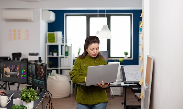 Employee holding laptop standing in creative agency office prosessing customer video project in post production software