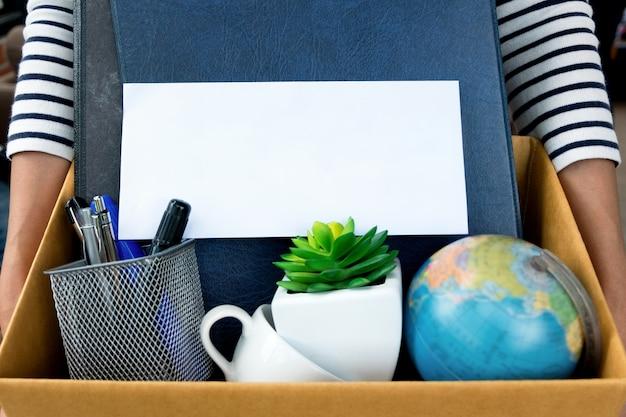 사직서를 들고 사무실을 떠나기 위해 상자를 포장하는 직원