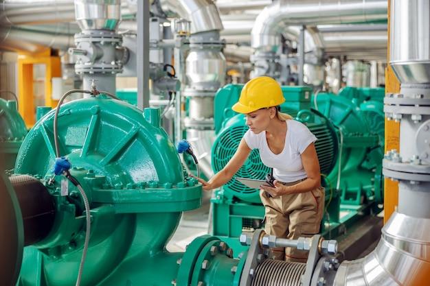 Сотрудник держит планшет и проверяет тепло на турбине, стоя на теплоцентрали