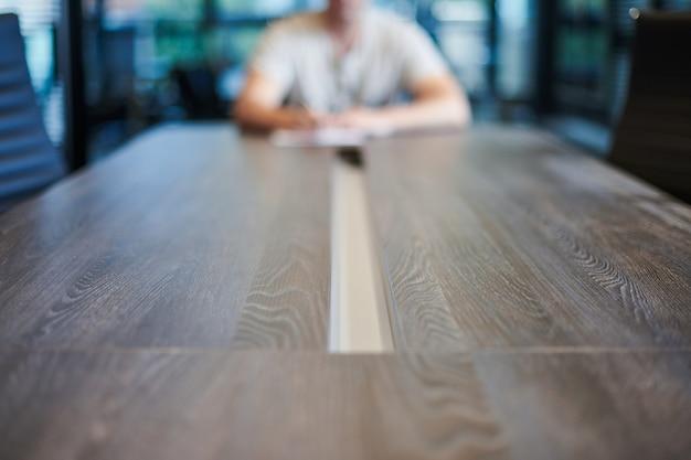Сотрудник в офисе конференц-зала. менеджер за столом в современном конференц-зале для деловых переговоров и деловых встреч. интервью с новым сотрудником.
