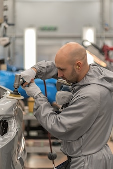 Сотрудник в цехе покраски кузова полирует окрашенные части кузова