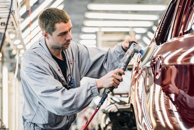 車のボディを塗装するショップの従業員が塗装されたボディパーツを磨く