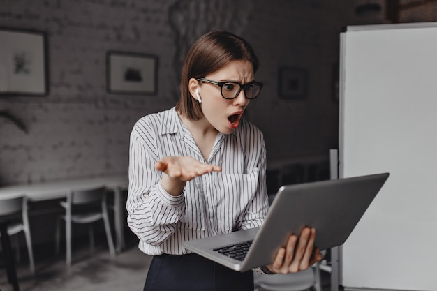 従業員は驚きと失望を持ってオープンラップトップを見ています。白いオフィスで眼鏡とヘッドフォンを持つビジネス女性の肖像画。