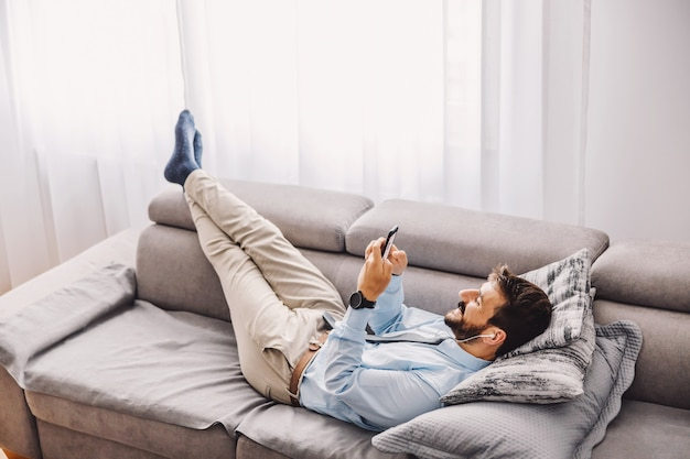 Employee lying down on the sofa and using mobile phone during quarantine. covid outbreak concept.