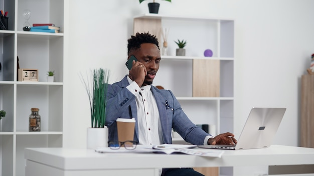 Сотрудник делает деловой звонок сосредоточены на ноутбуке на своем рабочем месте. клиент черного бизнесмена советуя с, обсуждая финансовый отчет. концепция переговоров и обсуждения контракта