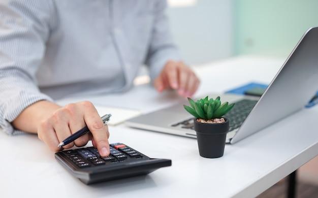Employee man finger press on calculator