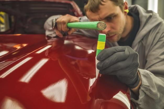 自動車工場の従業員が特別な手工具で小さな欠陥を修正します