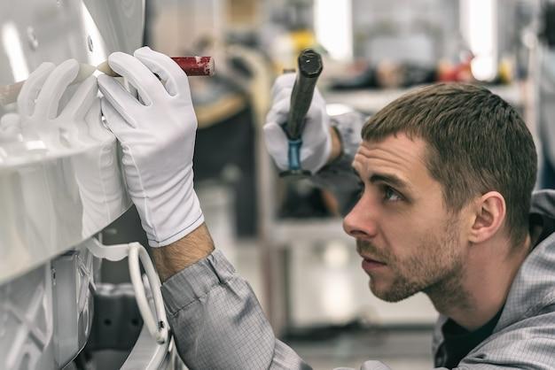 自動車工場の従業員が特別な手工具で小さな金属の欠陥を修正します