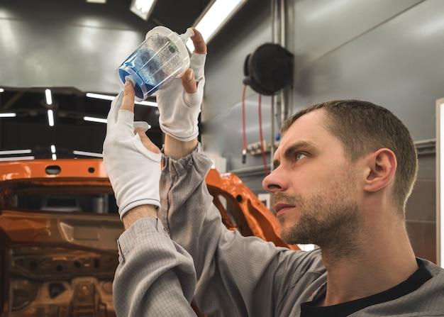 Сотрудник автозавода готовит базовую эмаль для покраски автомобилей.
