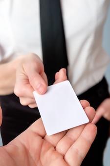 銀行の従業員は、プラスチックカード、クローズアップ、コピースペースを提供しています。プラスチック製のクレジットカードまたはビジネスカードを示すビジネス女性