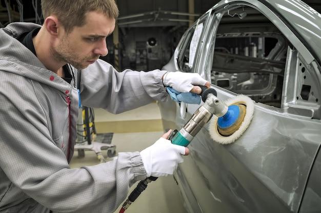 Сотрудник цеха покраски кузовов автомобилей полирует окрашенную поверхность на пневматической полировальной машине