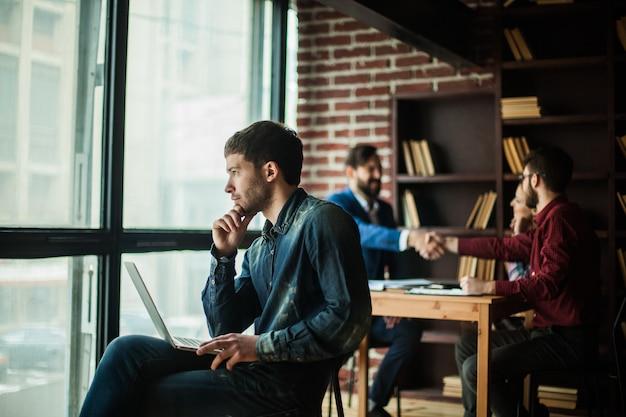 창 밖을 바라 보는 노트북을 가진 회사의 직원