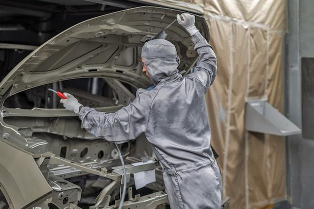 Сотрудник малярного цеха готовит кузов автомобиля к покраске.
