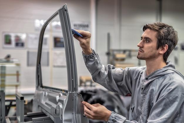 Сотрудник окрасочного цеха наклеивает кузов автомобиля декоративной пленкой на стойку двери.