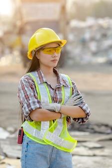 Сотрудник завода по переработке отходов стоит со скрещенными руками и готов к работе