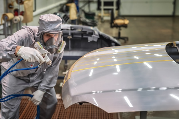 Employee of the paint shop of automobile factory conducts training on painting body parts