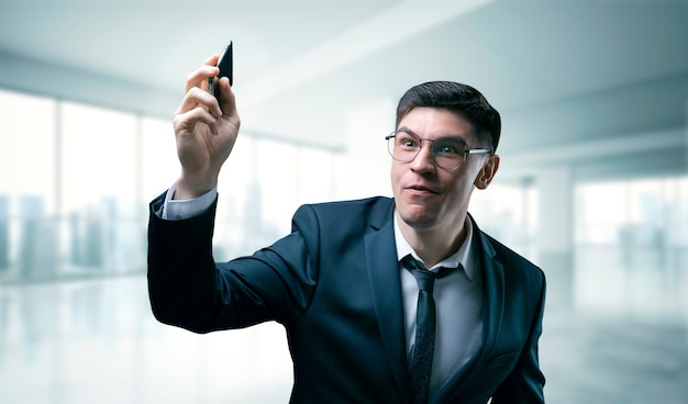 Employee recruiting agency holds out the phone. he is dressed in a stylish business suit.