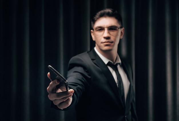 Агентство по подбору персонала протягивает телефон. он одет в стильный деловой костюм.