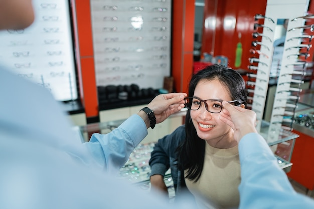 An employee's hand is helping to put on a pair of glasses that a woman who has done an eye exam has chosen at an eye clinic