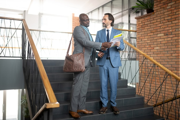 보고서를 보여주는 직원. 계단에 서서 상사에게 보고하는 검은 피부의 직원
