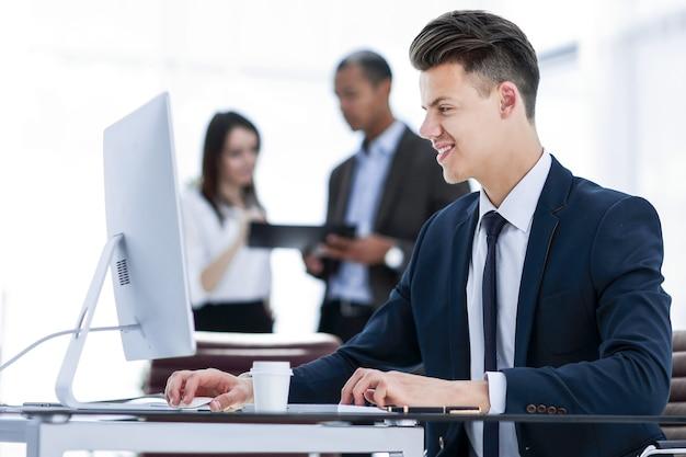 オフィスの机の後ろに座っている従業員。コピースペース付きの写真